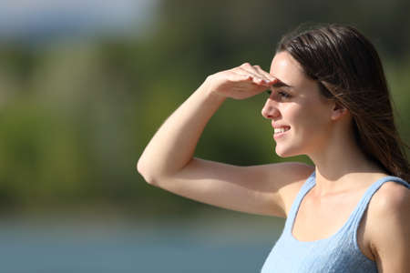 Happy woman looking away protecting from sun with the hand on forehead in a lake