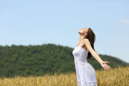 Profile of a woman breathing fresh air in a wheat field on summer