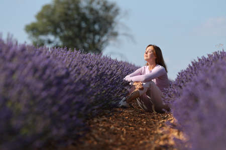 Relaxed woman resting sitting in a lavender field with closed eyes