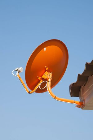 antena parabolica: The orange satellite dish with the blue sky background