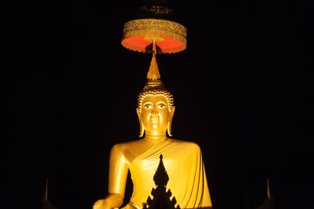Golden buddha image with night time in thai temple Stock Photo