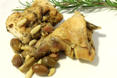 rabbit meat cooked with olives and pine nuts