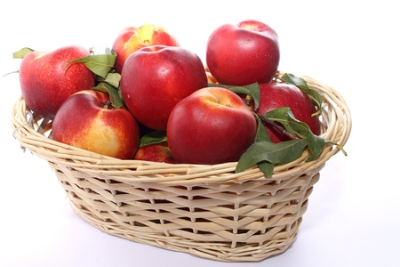 nectarine peaches inside a wicker basket