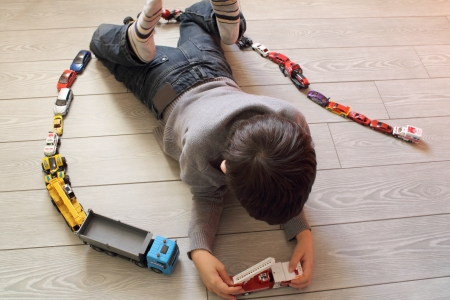 Young boy playing with toy cars photo