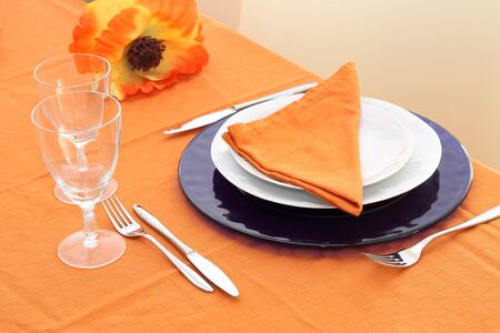 Table setting on orange table cloth