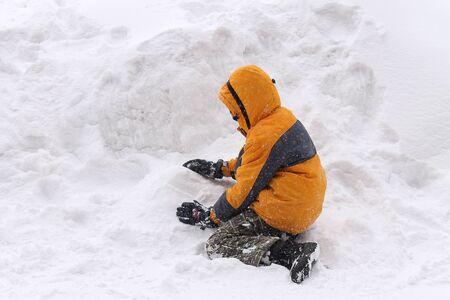 snowdrift: Young boy playing in a snowdrift