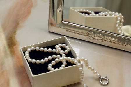 Pearl necklace in a gift box in front of a mirror photo