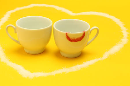Two cups of coffee inside a heart, one of them with lipstick Stock Photo