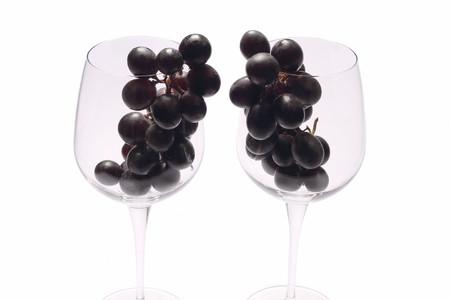 Black grapes into wine glasses