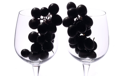 Black grapes into wine glasses