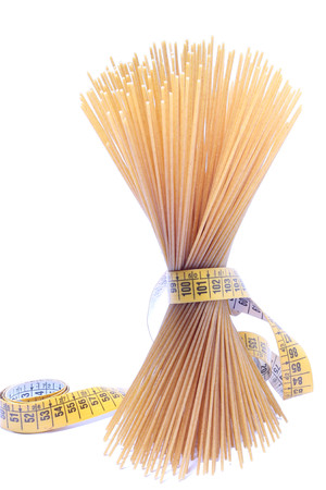 Wholemeal spaghetti and centimeter isolated on white