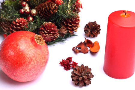 Christmas composition with red candle and pomegranate photo