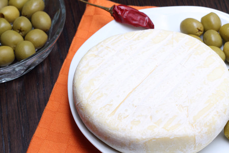Cheese with green olives and red chili peppers photo