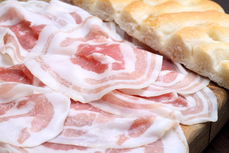 Bacon slices with focaccia on wooden cutting board photo