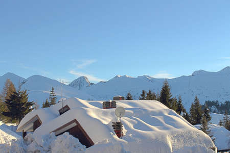Snow-covered roofs in mountain landscape photo