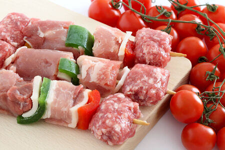 Raw meat skewers with cherry tomatoes photo