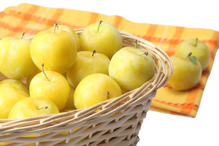 Yellow plums in wicker basket photo