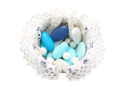 Blaue und weiße gebrannte Mandeln in der Schüssel mit Spitze bedeckt