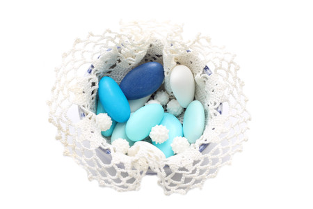 bonbonniere: Blue and white sugared almonds in bowl covered with lace