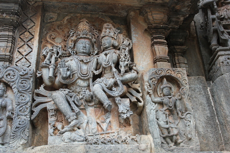 Hoysaleswara Temple Wall Carving of Lord Shiva with his wife Parvati and holding japa mala or rosary beads