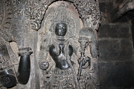 Delicately carved lady (fanning lady) sculpture at hoysaleswara temple