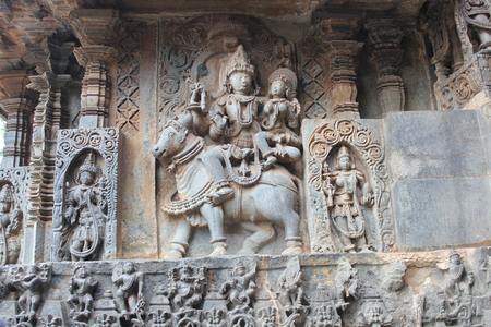 Hoysaleswara Temple outer wall carved with sculpture of lord shiva and parvati Stock Photo
