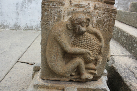 carving of a monkey holding a fruit on the pillar of the Gommateshwara Temple Stock Photo