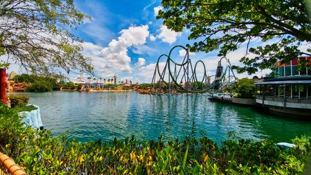scenic view of roller coaster rides across the blue lake surrounded by trees and bushes on a bright sunny day in Universal studios florida. Фото со стока - 129706419