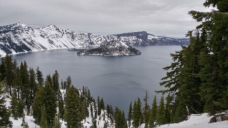 winter snowy scene of crater lake in oregon, with snow covered mountains green pine trees overcast foggy sky in background. Фото со стока
