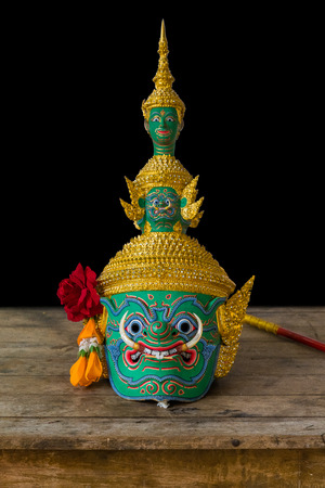 The mask of Thotsakan or Ravana, one of the demon king in Thai Ramayana pantomime on the wooden table isolated on black background