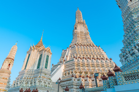 The spire of Wat Arun Ratchawararam with clear blue sky