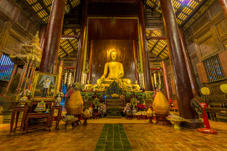 Inside the wooden temple of Wat Phan Tao showing the image of golden Buddha.