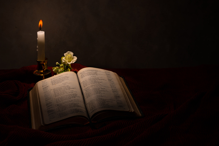 Reading the bible under the candle light on the candlestick Stock Photo