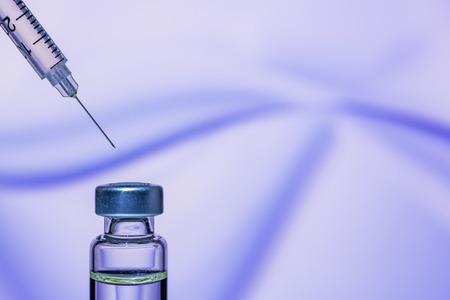 Eine Spritze mit der Nadel zeigt auf die Impfstoffflasche auf dem bunten abstrakten Hintergrund Standard-Bild