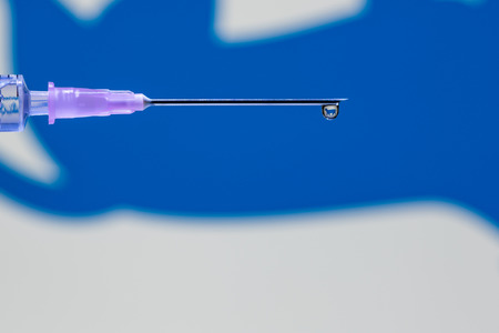 A droplet of vaccine at the tip of the needle and syringe reflecting blue dog symbol