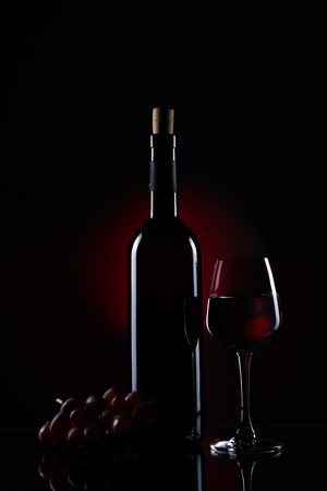 A bottle of red wine with grape vine and a half full wine glass using stripbox for rim light effect