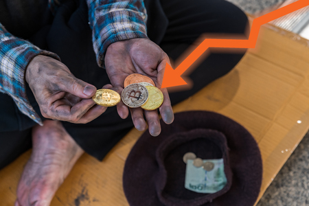 Handful of bitcoin coins in a beggar's hands with orange line graph pointing downward - devaluation of bitcoin concept
