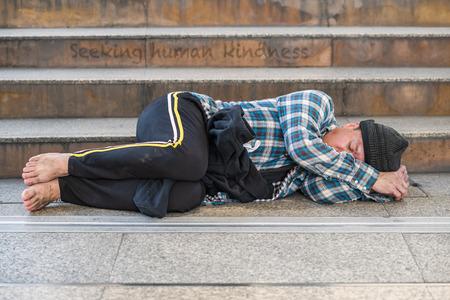 A male homeless beggar sleeping near the staircase in urban area