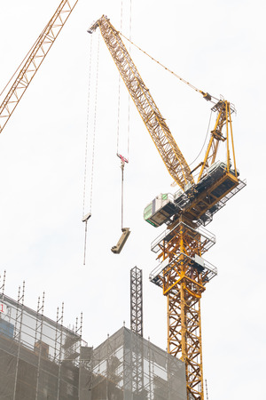 Construction cranes at work to construct a tall building in Bangkok