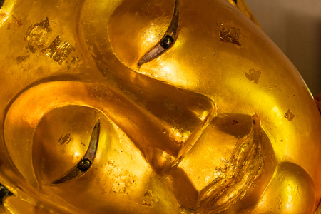Close-up face of sleeping Buddha statue from a temple in Chiang Mai, Thailand