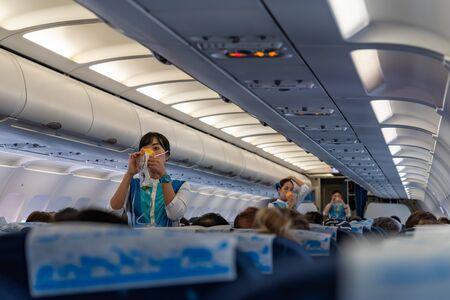 SUVARNABHUMI AIRPORT, BANGKOK, THAILAND - MARCH 23, 2019 : Flight attendants demonstrate the proper use of oxygen masks before flight Redactioneel