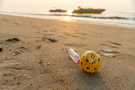 Plastic garbage on a beach with boats on background