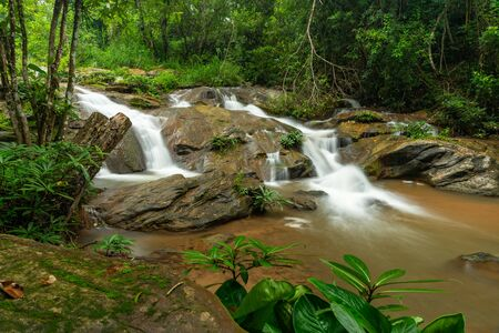 Water cascading from layer of large rocks of Mae Sa Noi waterfall with misty water effect