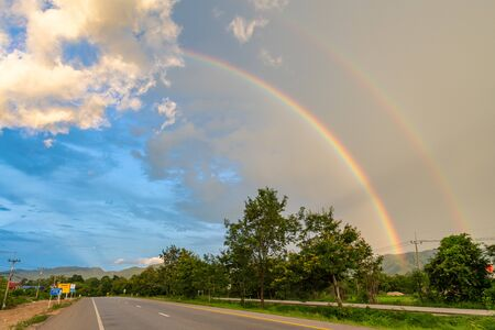 Double rainbow appearing after rain seen from roadside near Lampang province of Thailand Imagens