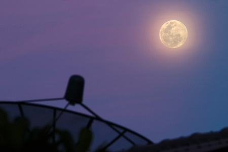 waxing gibbous: Full moon with foreground Silhouette Satellite dish blurred Stock Photo