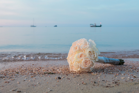 roses bouquet on the beach in twilight