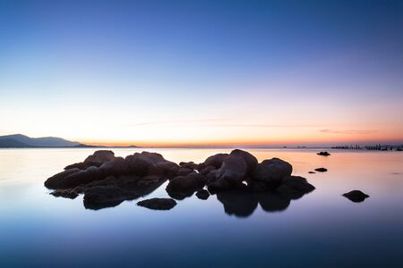 A dramatic scenic landscape shot of the rocks in the ocean with beautiful sky and mountain in background, on a tropical island, shooting in long exposure mode during summer time Stock Photo