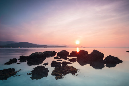 A dramatic scenic landscape shot of the rocks in the ocean with beautiful sky and mountain in background, on a tropical island, shooting in long exposure mode during summer time, Samui Island Thailand Stok Fotoğraf