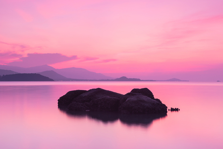 A dramatic scenic landscape shot of the rocks in the ocean with beautiful pink sky and mountain in background, on a tropical island, shooting in long exposure mode, Samui island Thailand Stok Fotoğraf