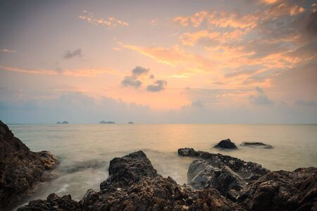 A dramatic scenic landscape shot of the rocks in the ocean with beautiful sky and mountain in background, on a tropical island, shooting in long exposure mode, Samui island Thailand